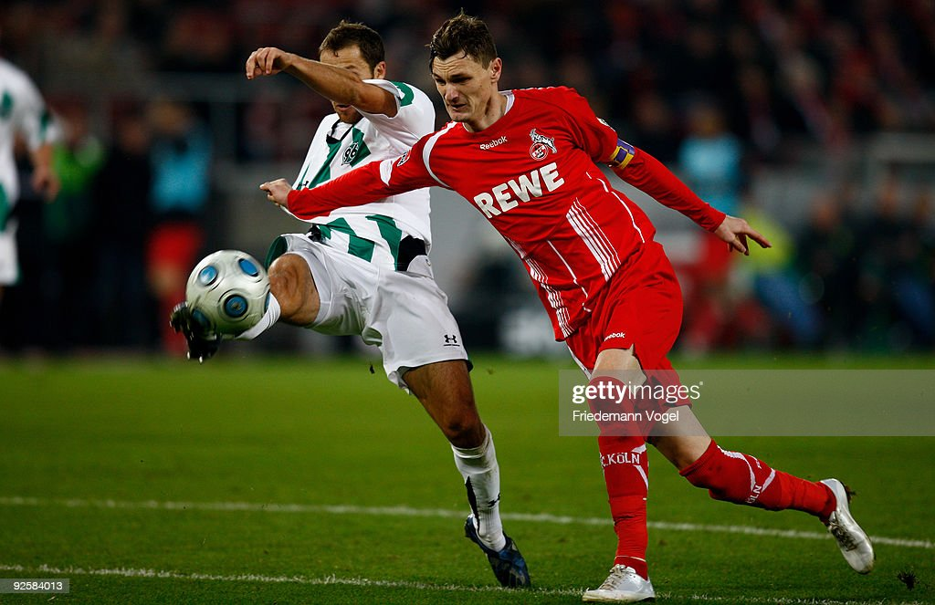 Milivoje Novakovic of Koeln in action with Steven Cherundolo of Hannover during the Bundesliga match between 1 FC Koeln and Hannover 96 at the Rhein...