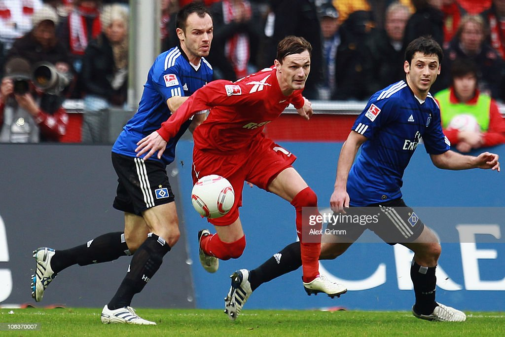 Milivoje Novakovic (C) of Koeln is challenged by Heiko Westermann (L) and Tomas Rincon (R) of Hamburg during the Bundesliga match between 1 FC Koeln and Hamburger SV at the RheinEnergieStadion on October 30, 2010 in Cologne, Germany.