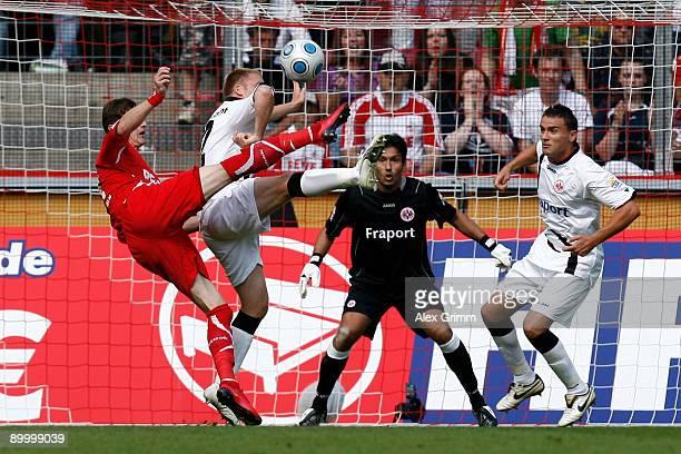 Milivoje Novakovic of Koeln tries to score a goal against Patrick Ochs goalkeeper Oka Nikolov and Aleksandar Vasoski of Frankfurt during the...