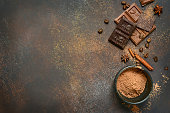 Milk and bitter chocolate with cocoa and spices on a rusty metal or slate background.Top view with copy space.