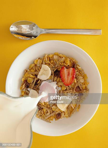 Milk being poured into bowl of cereal, overhead view
