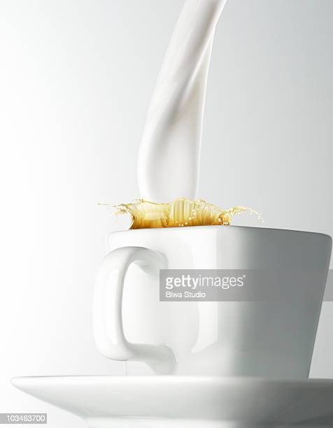 milk being poured into coffee cup