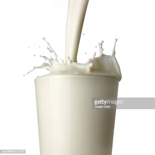 Milk being poured into glass, white background