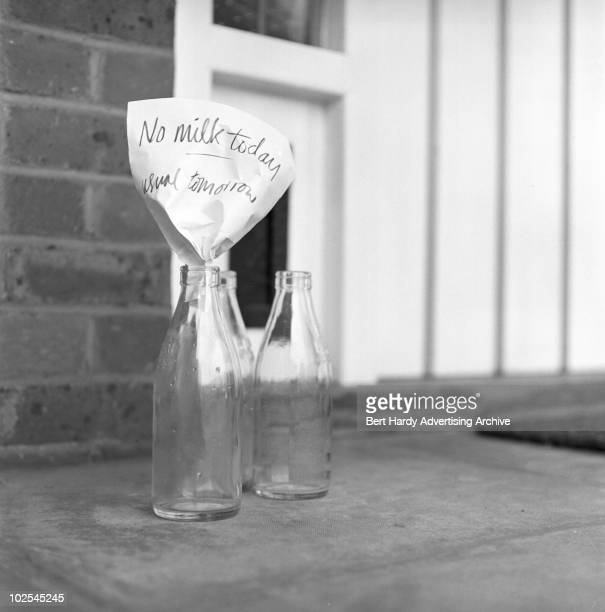 A milk bottle on a doorstep with a note to the milkman reading 'No milk today usual tomorrow' 10th July 1963