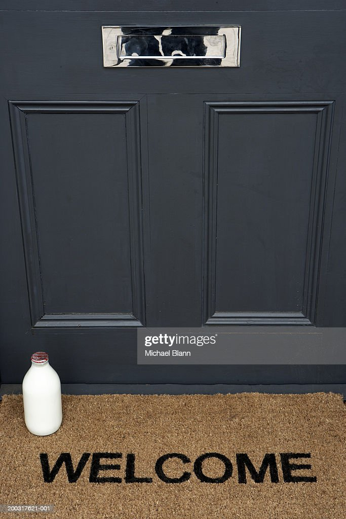 Milk bottle on welcome mat by front door, close-up : Stock Photo