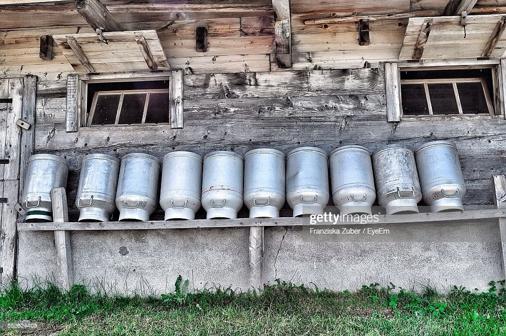Milk Cans In Front Of Farm Building