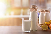 Milk containers on wooden table in sunny rustic kitchen. Horizontal composition. Front view