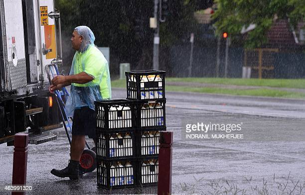 A milk delivery man takes out crates from his truck amidst rain from Tropical Cyclone Marcia in Brisbane on February 21 2015 Australia was on...