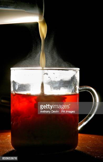 Milk is poured into a cup of tea