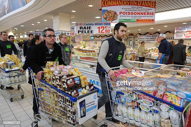 Milk producers push trolleys filled with dairy products of French group Lactalis during an action on December 6 2013 in a supermarket of Le Mans to...