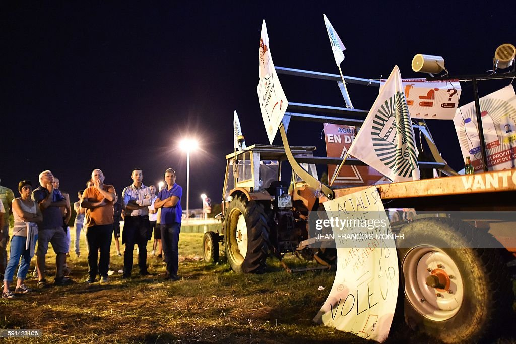 Milk producers stand next to a truck with a placard reading 'Lactalis ruins his producers' outside the Lactalis group headquarters in Change near...