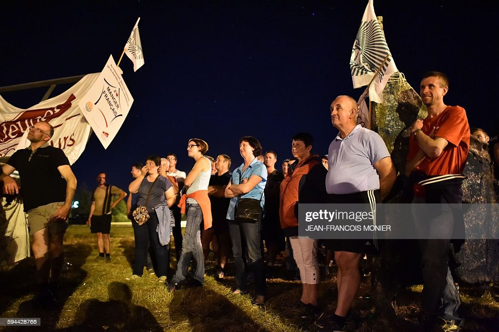 Milk producers stand outside the Lactalis group headquarters in Change near Laval northwestern France as part of a protest for a fairer milk price on...