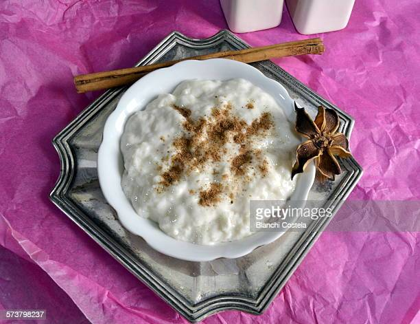 Milk rice pudding in pot with cinnamon on pink