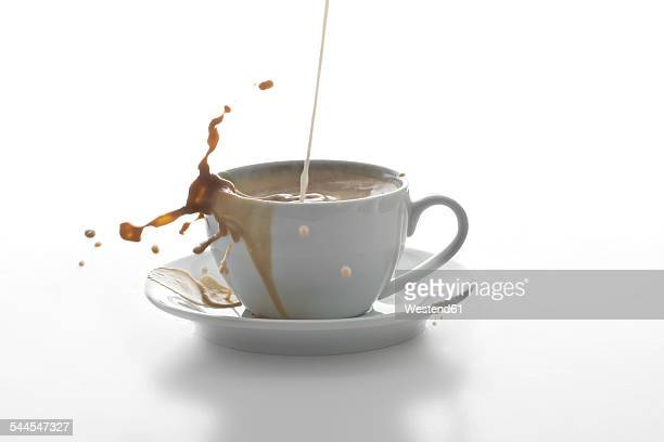 Milk splashing in a cup of coffee in front of white background