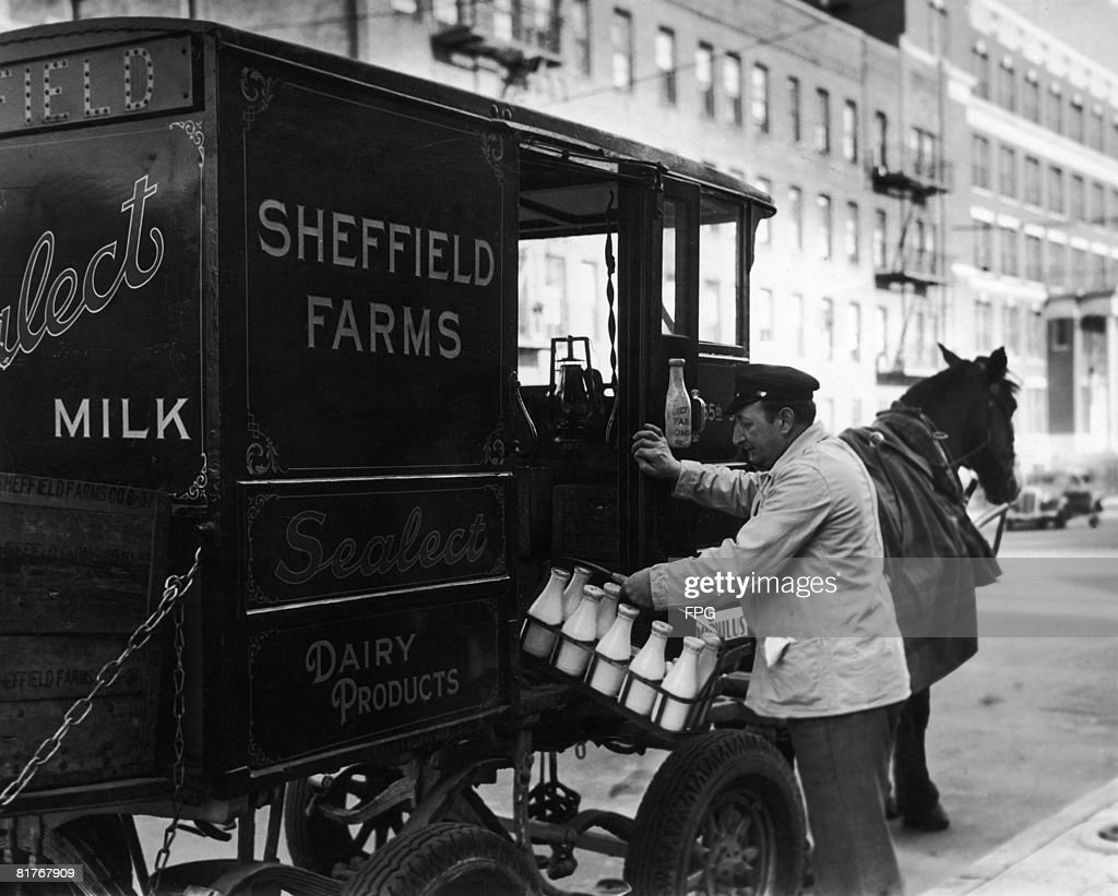 A milkman delivering milk from the Sheffield Farms Milk Company, with a horsedrawn cart, New York, circa 1930.