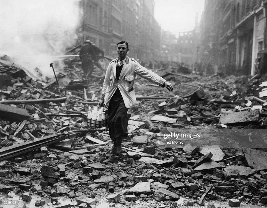 A milkman delivering milk in a London street devastated during a German bombing raid. Firemen are dampening down the ruins behind him.