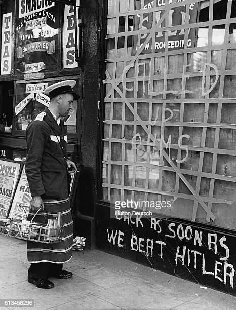 A milkman looks the handpainted sign on a closed store in South London The storefront window reads 'Called up OHMS Back as Soon as We Beat Hitler'...