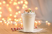 Jar of Christmas milk drink on wooden rustic table with winter holiday background. Milkshake on the background of the New Year's garland