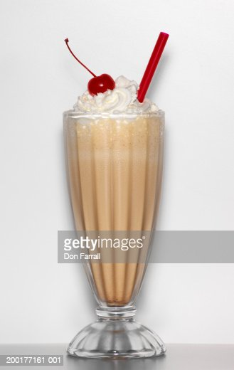 Milkshake with whipped cream and cherry garnish