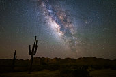 The Milky Way shines brightly in the night sky against a Saguaro cactus silhouette in the Sonoran Desert near Phoenix, Arizona.