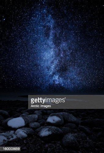 Milky way galaxy over rocky coastline