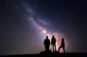 Milky Way. Night sky with stars and silhouette of a happy family with raised-up arms