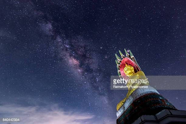 Milky Way over gold Buddha statue, temple name is Wat Nang Lao in Songkhla, Thailand.