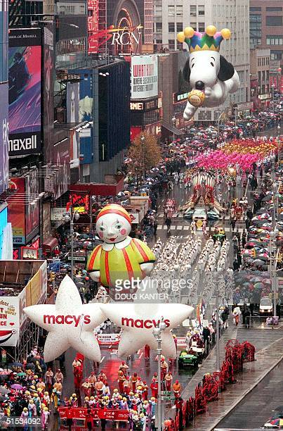 Millenium Snoopy moves into Times Square behind Cloe the Clown and the Macy's Star Balloon in New York during the Macy's Thanksgiving Day Parade 25...