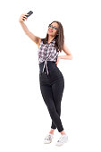 Millennial female stylish hipster girl smiling and posing for taking selfie. Full body isolated on white background.
