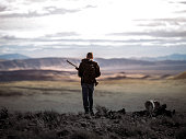 Millennial Hunter with a Yellow Lab hunting dog walking in the rugged Nevada desert.