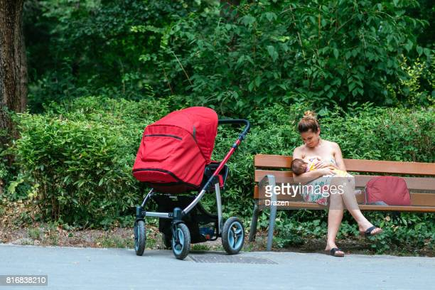 Millennial mother and baby breastfeeding in summer outdoors