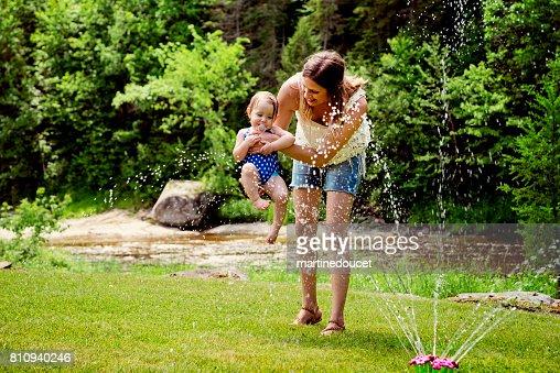 Millennial mother enjoying springkling water with baby daughter. : Stock Photo
