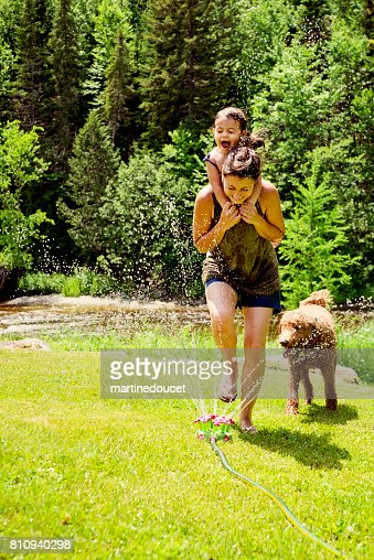 Millennial mother enjoying springkling water with baby daughter. : Stock Photo