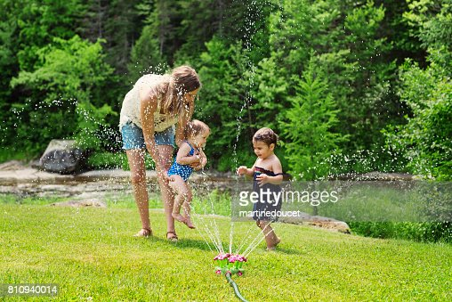 Millennial mother enjoying springkling water with baby daughters. : Stock Photo