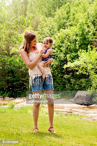 Millennial mothers enjoying springkling water with baby daughter. : Stock Photo