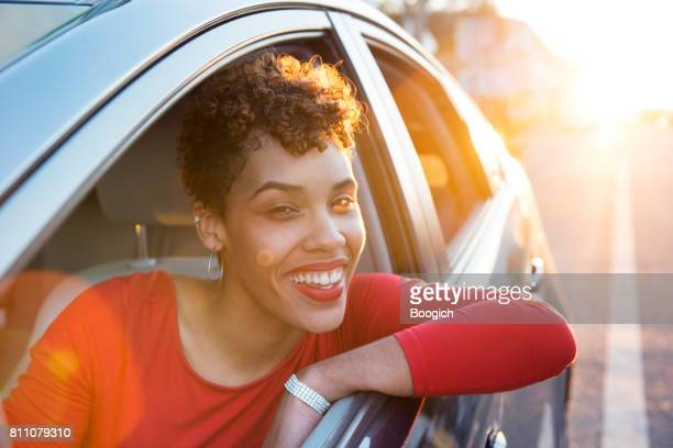 Millennial Rideshare Driver Waiting for Passenger in Car at Sunset