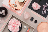 Rose quartz background with several decorative objects, gemstones, seashells and candle.