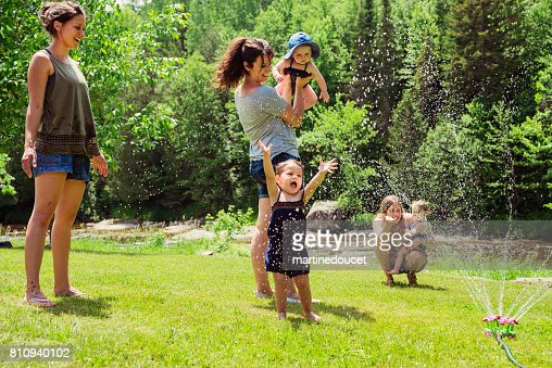 Millennials mothers enjoying springkling water with baby daughters. : Stock Photo