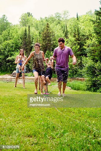 Millennials parents enjoying springkling water with baby daughters. : Stock Photo