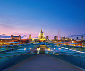 Millennium Bridge leading to Saint Paul's Cathedral in central London. Panoramic image taken at sunset.