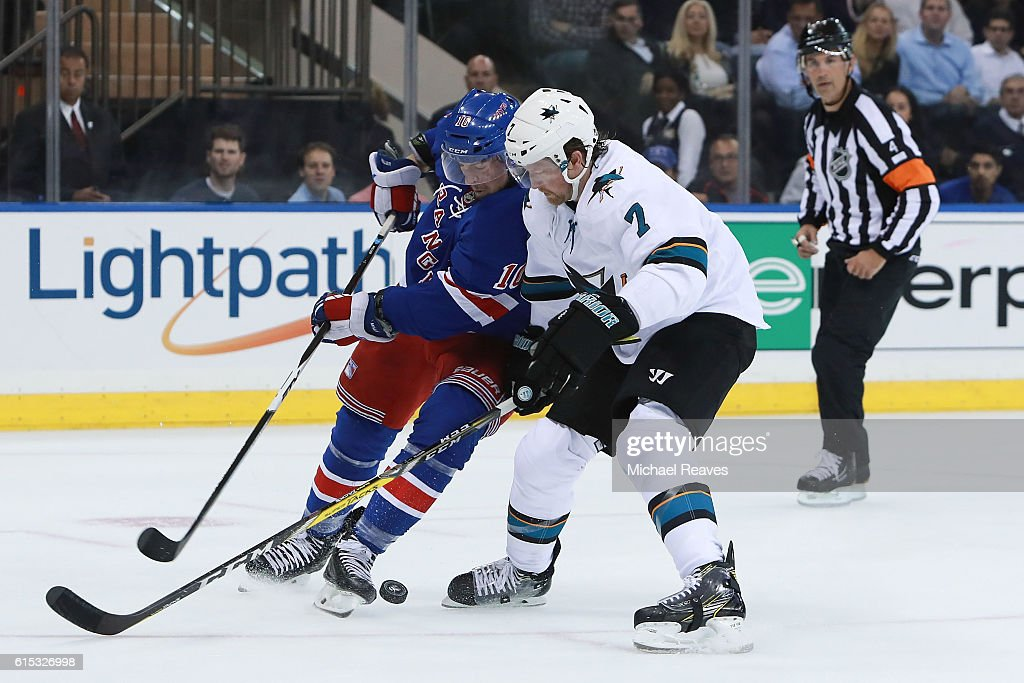 J.T. Miller #10 of the New York Rangers fights for the puck with Paul Martin #7 of the San Jose Sharks during the second period at Madison Square Garden on October 17, 2016 in New York City.