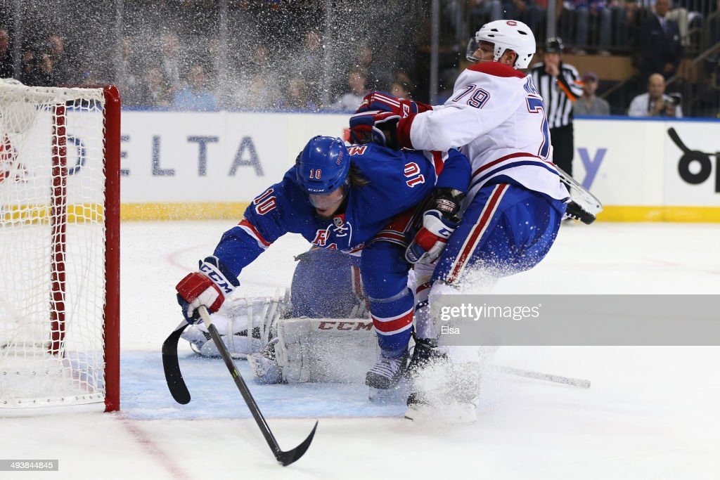 T Miller of the New York Rangers gets checked into the goal post by Andrei Markov of the Montreal Canadiens in the second period during Game Four of...