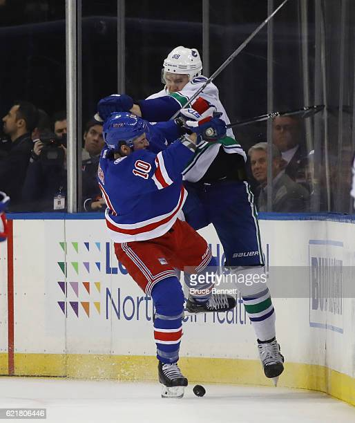 T Miller of the New York Rangers is checked by Nikita Tryamkin of the Vancouver Canucks during the third period at Madison Square Garden on November...