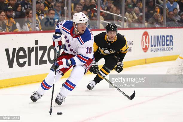 T Miller of the New York Rangers looks for a open teammate in front of Brian Dumoulin of the Pittsburgh Penguins during the first period at PPG...