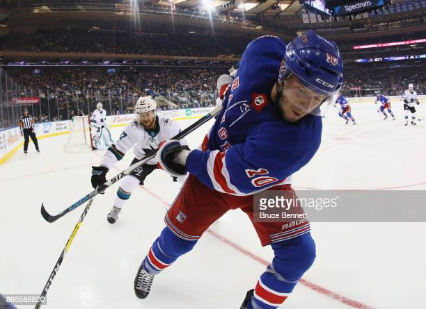 T Miller of the New York Rangers shoots the puck away from Joakim Ryan of the San Jose Sharks during the third period at Madison Square Garden on...