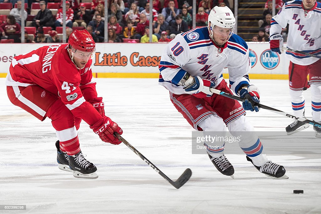 J.T. Miller #10 of the New York Rangers skates up ice with the puck followed by Luke Glendening #41 of the Detroit Red Wings during an NHL game at Joe Louis Arena on January 22, 2017 in Detroit, Michigan.