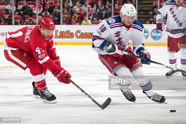 T Miller of the New York Rangers skates up ice with the puck followed by Luke Glendening of the Detroit Red Wings during an NHL game at Joe Louis...