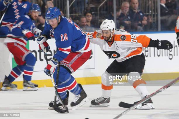 T Miller of the New York Rangers skates with the puck against PierreEdouard Bellemare of the Philadelphia Flyers at Madison Square Garden on April 2...