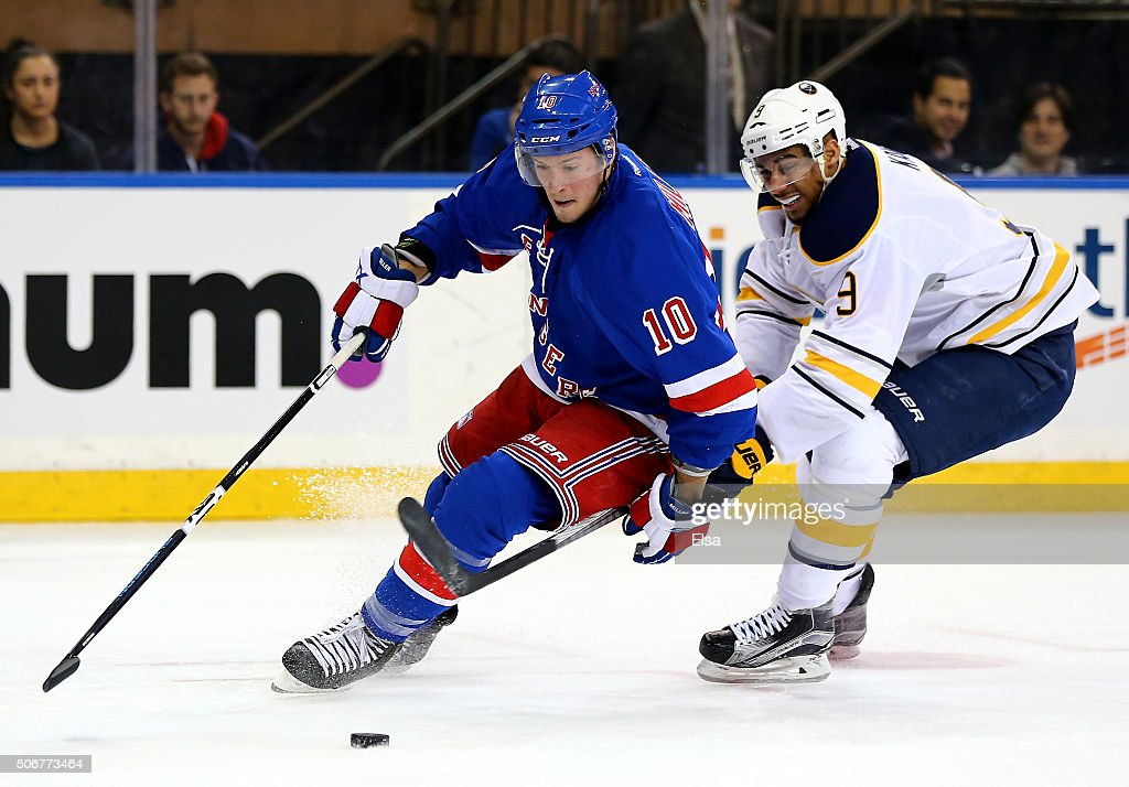 T Miller of the New York Rangers tries to keep the puck from Evander Kane of the Buffalo Sabres at Madison Square Garden on January 25 2016 in New...
