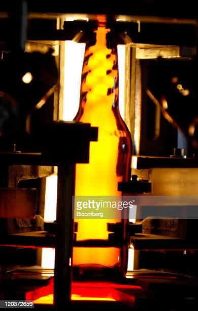 A MillerCoors Miller Lite vortex bottle exits a forming machine at the OwensIllinois Inc glass manufacturing plant in Waco Texas US on Thursday Aug 4...